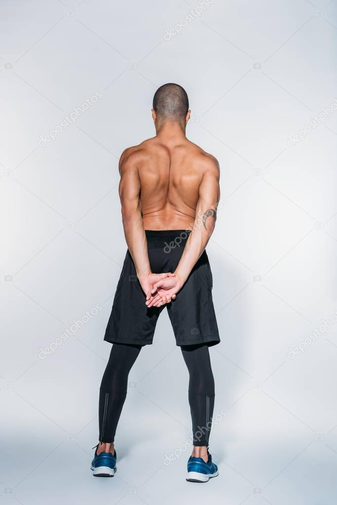 rear view of shirtless african american sportsman stretching back