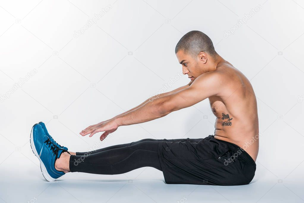african american sportsman stretching and sitting on floor