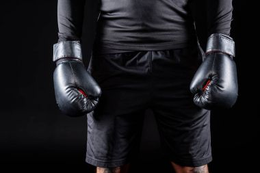 cropped shot of boxer in black gloves isolated on black
