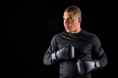 young african american boxer in sportswear and black gloves isolated on black