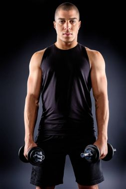 handsome african american sportsman with dumbbells on black