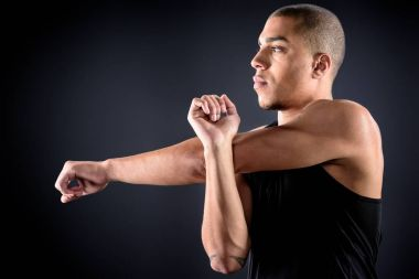 young african american sportsman stretching arms on black