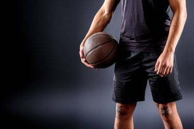 cropped shot of basketball player holding ball on black