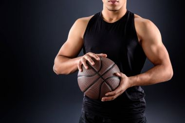 cropped shot of african american basketball player with ball on black