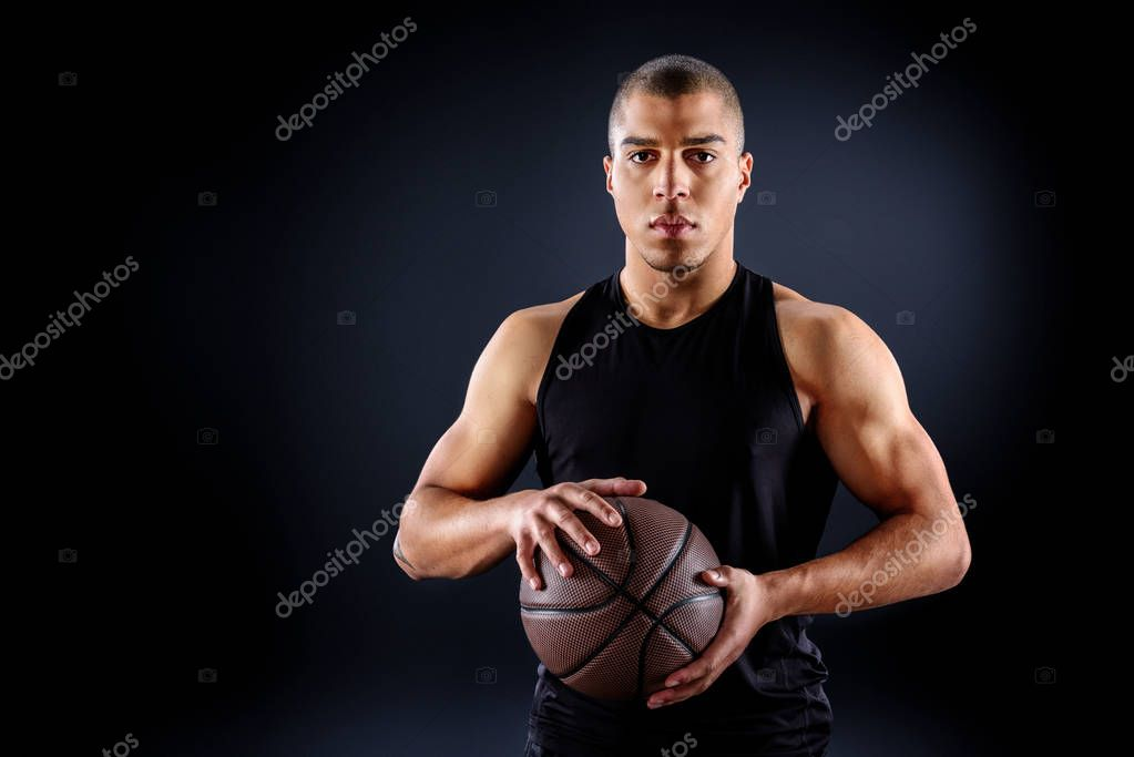handsome african american basketball player with ball isolated on black