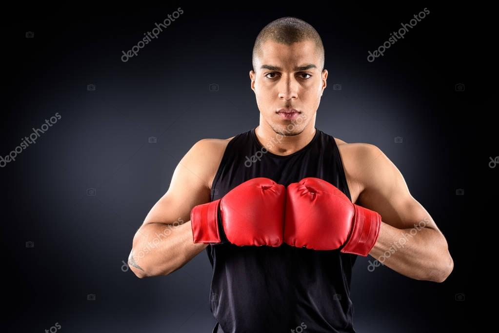 handsome african american sportsman in boxing gloves looking at camera on black