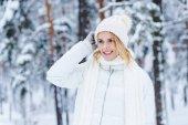 Porträt einer schönen glücklichen Frau im verschneiten Winterwald