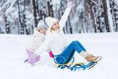 boldog lánya és anyja együtt szánkózás télen Park