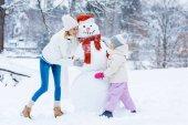 šťastný matka a dcera dělat sněhuláka dohromady v zimě lese