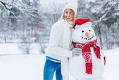 Fotografie portrét mladé ženy veselá stál sněhulák a při pohledu na fotoaparát
