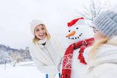 šťastný matka a dcera stál sněhulák společně v zimě lese