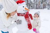 šťastný matka a dcera hraje s sněhulák v zimě parku