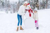 krásná šťastná matka a dcera se usmívá na kameru stoje s sněhulák v zimě parku
