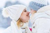 boční pohled na krásná šťastná matka a dcera usmívala se navzájem v destinaci winter park
