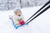 cute little child lying on sled and smiling at camera in winter park