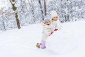 šťastný matka a roztomilá malá dcera dělat sněhuláka dohromady v destinaci winter park