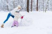 boční pohled na happy matka a dcera dělat sněhuláka v zimě parku