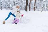 Fotografie šťastný matka a dcera dělat sněhuláka a usmívá se na kameru v destinaci winter park