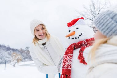 happy mother and daughter standing near snowman together in winter forest