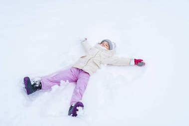 cute little child in warm clothes making snow angle