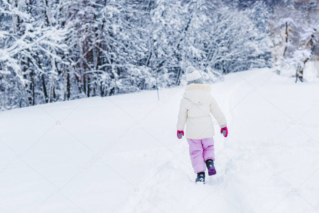 back view of little child in warm clothes walking on snow in winter park