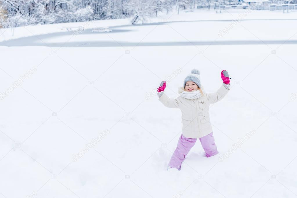 adorable happy child with raised hands in mittens standing in snow and smiling at camera in winter park