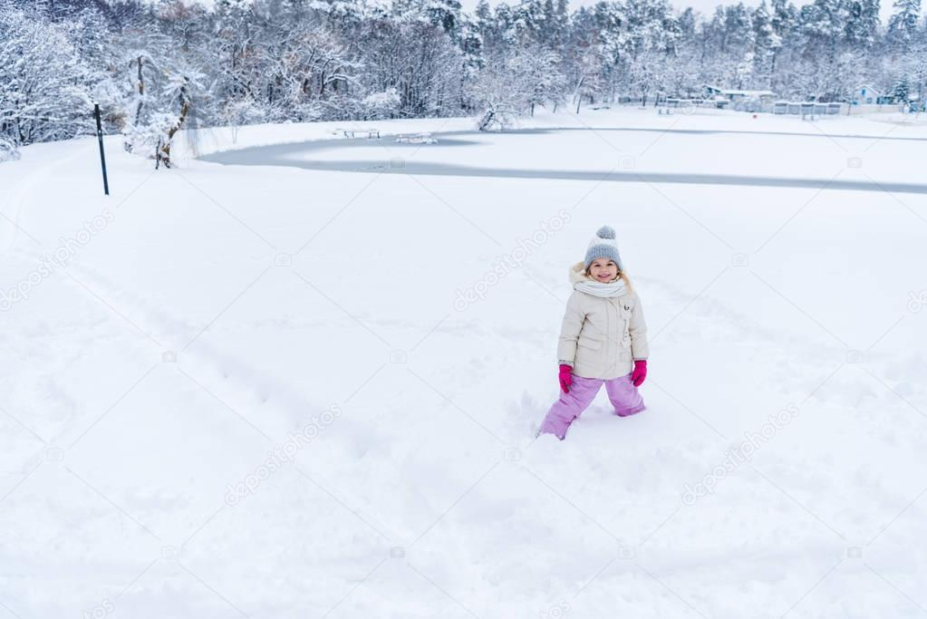 adorable happy child standing in snow and smiling at camera in winter park