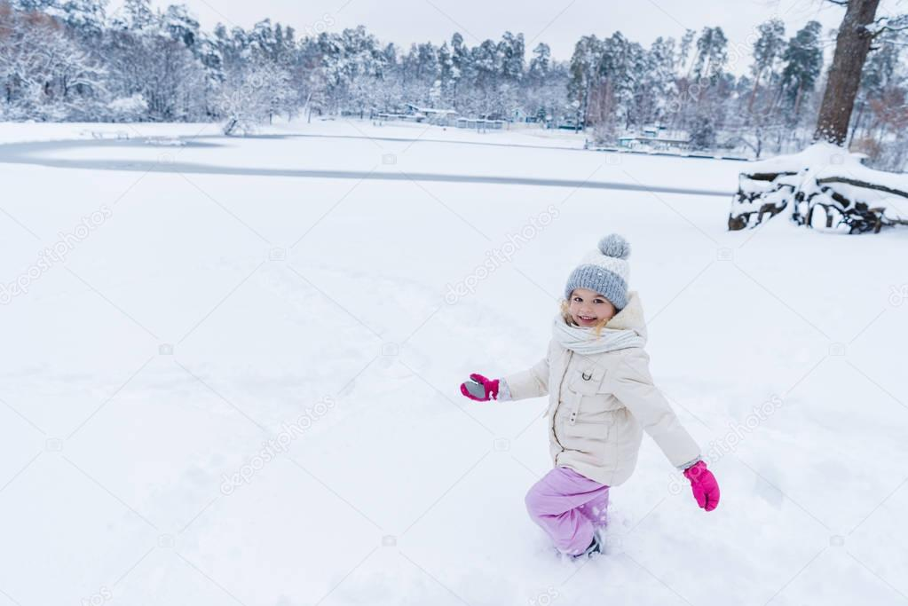 adorable happy kid playing in snow and smiling at camera in winter park