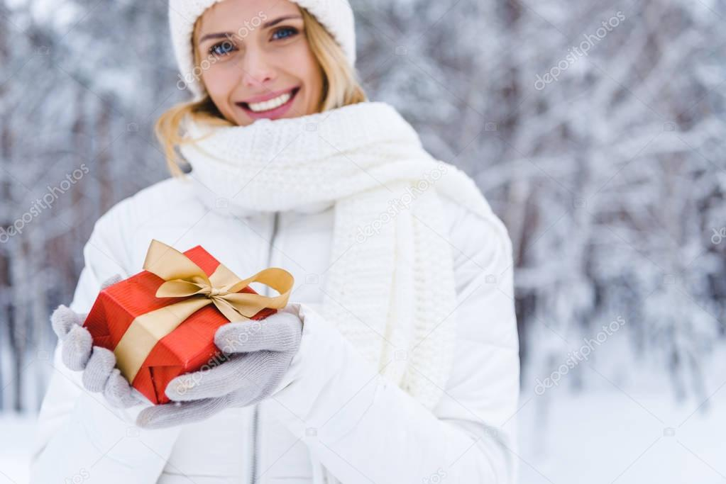 happy woman holding gift box and smiling at camera in winter park