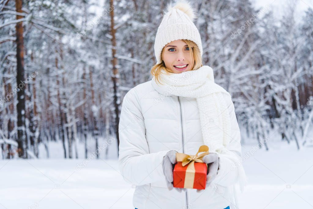 beautiful young woman holding gift box and smiling at camera in winter park