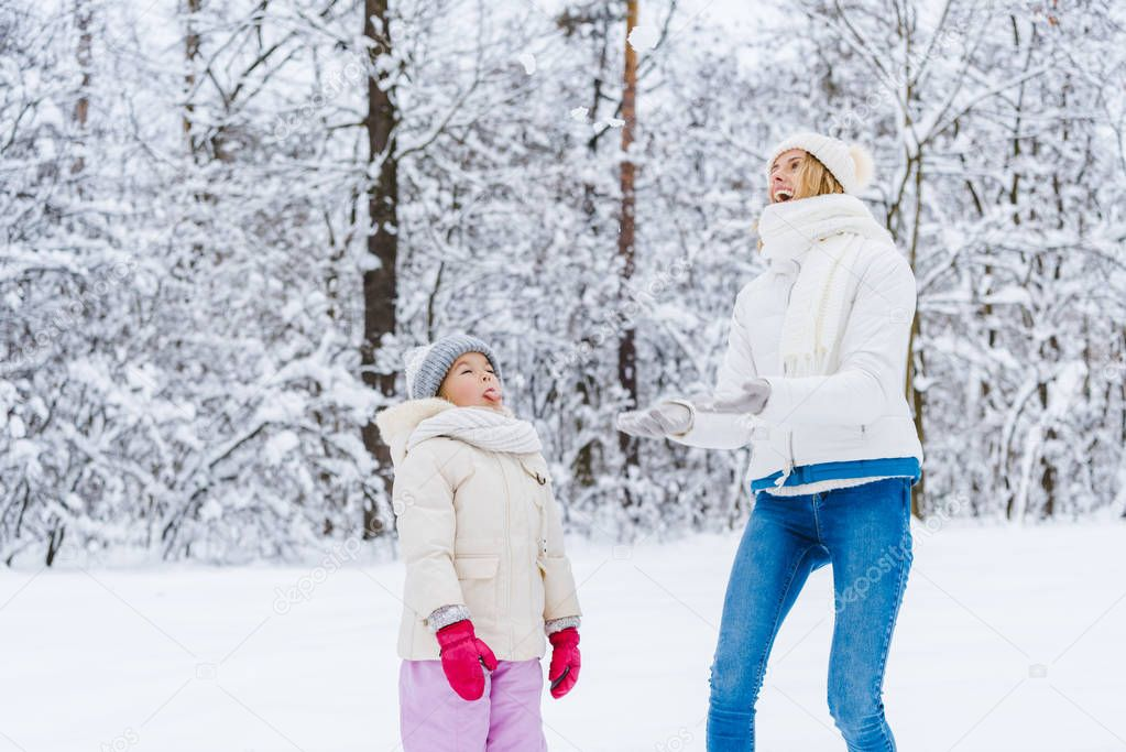 beautiful happy mother and daughter looking up while playing together in winter park