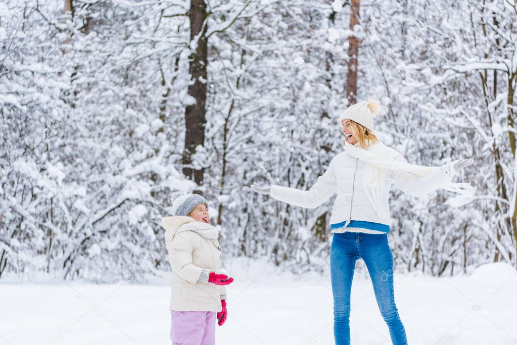 beautiful happy mother and daughter playing together in winter park