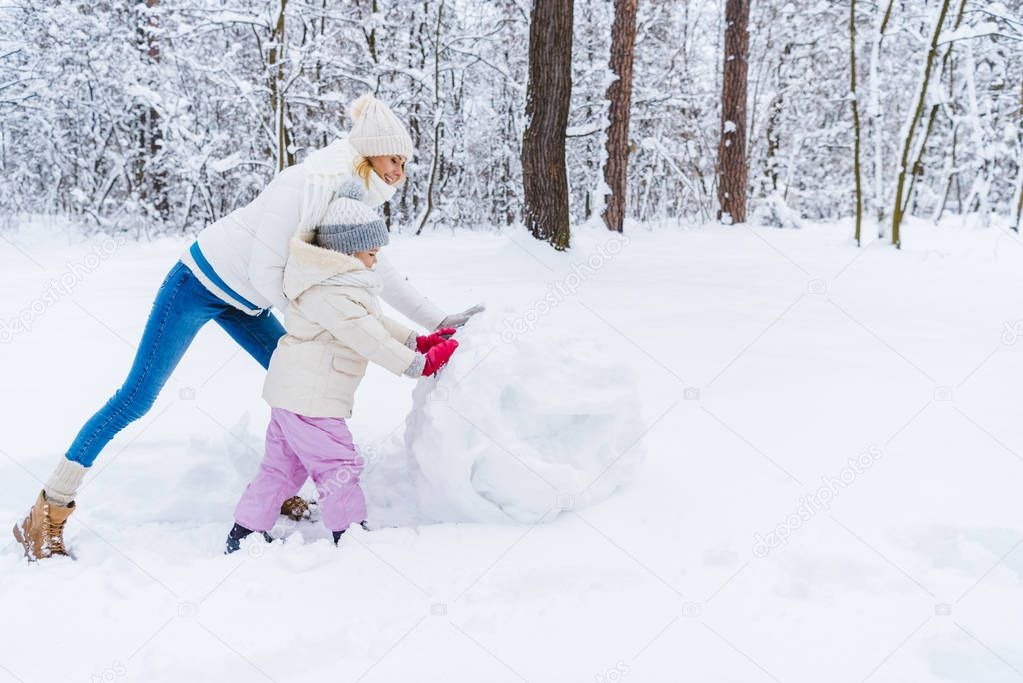 side view of happy mother and daughter making snowman in winter park