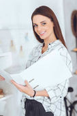 Photo attractive businesswoman holding folder and looking at camera