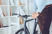 cropped image of businessman holding bike in office