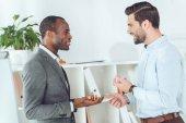 s úsměvem africké americké a kavkazské podnikatelé mluví o úřadu