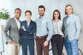 Fotografie s úsměvem multikulturní podnikatelé stál a díval se na kameru