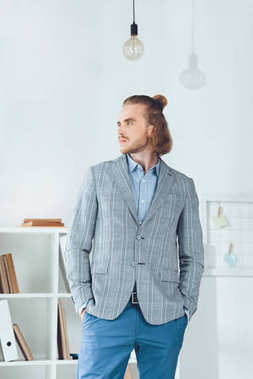 handsome businessman standing in office and looking away
