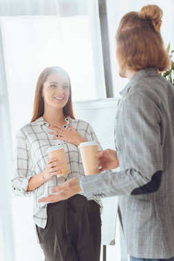 male and female colleagues talking during coffee break in office