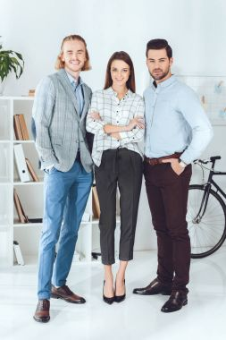 smiling caucasian businesspeople standing in office and looking at camera