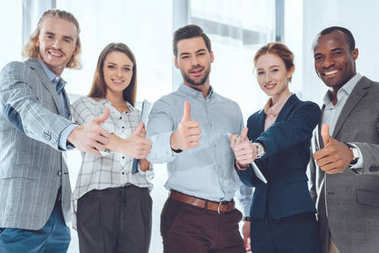 smiling multicultural businesspeople showing thumbs up