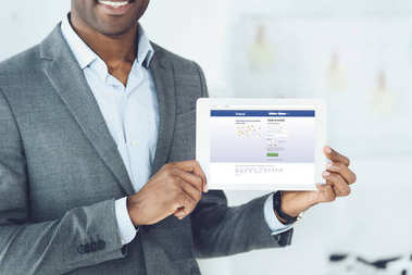 cropped image of smiling african american man showing tablet with loaded facebook page
