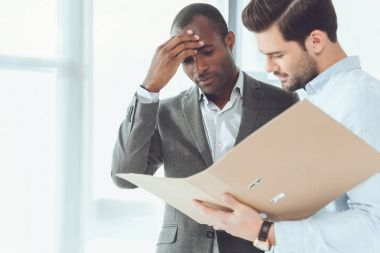 african american and caucasian businessmen looking at documents in folder