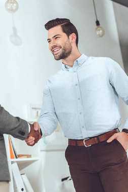Cropped image of african american and caucasian businessmen shaking hands stock vector