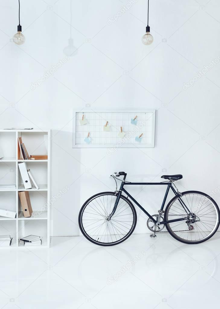 bicycle near wooden shelves in empty office