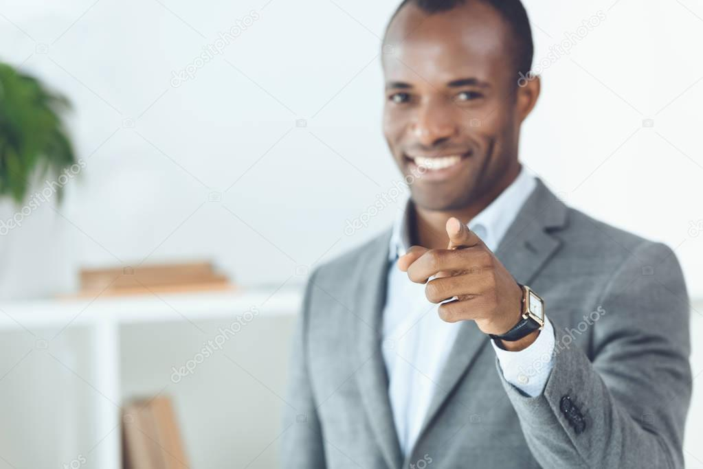 smiling african american man pointing on camera