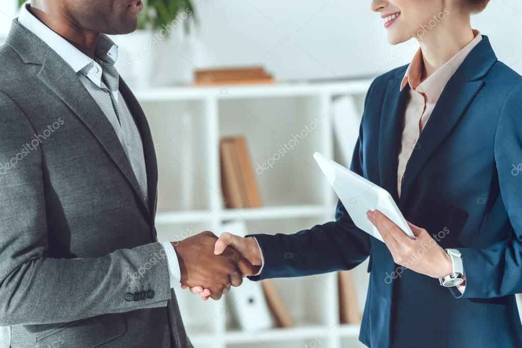 cropped image of african american businessman and businesswoman shaking hands