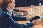 woman holding digital tablet while sitting at table