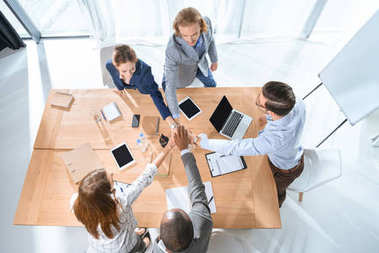 Business team shaking hands over table at office space stock vector