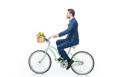 side view of groom in suit riding retro bicycle isolated on white